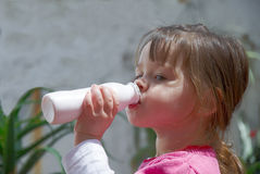 Little girl drinking yogurt Stock Photos