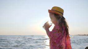 Little girl in hat drinks clean water near sea with waves in backlight, close-up cute child keeps cup in hands at sunset. Little girl drinks clean water keeps stock video footage