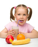 Little girl drinks fruit juice Stock Images