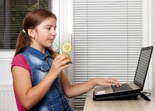 Little girl drinks juice and works on the laptop Stock Images