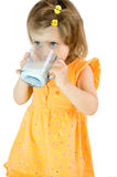 The little girl drinks milk. The little girl greedy drinks milk Stock Photos