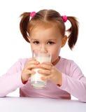 Little girl drinks milk. Cute little girl drinks milk, isolated over white Stock Images