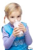 Little girl drinks milk. Little blonde girl in blue dress drinks milk, isolated on white background Royalty Free Stock Photos