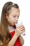 Little girl drinks milk. Little girl in red dress drinks milk, isolated on white background Royalty Free Stock Image