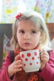 Little girl drinks milk. From a big mug Royalty Free Stock Image