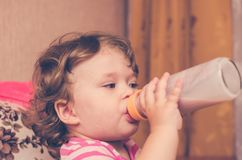 Little girl drinks milk from a bottle.  Stock Photos