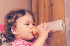 Little girl drinks milk from a bottle.  Royalty Free Stock Photos