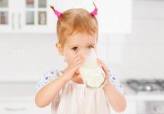 Little girl drinks milk. Child at breakfast a little girl drinks milk Stock Photo