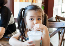 Little girl drinks milk at coffee shop Royalty Free Stock Image