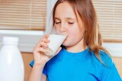 Little girl drinks milk Stock Images