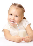 Little girl drinks milk using drinking straw. Cute little girl drinks milk using drinking straw, isolated over white Royalty Free Stock Photo
