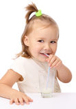 Little girl drinks milk using drinking straw Royalty Free Stock Photos