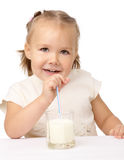 Little girl drinks milk using drinking straw Royalty Free Stock Photography