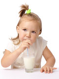 Little girl drinks milk using drinking straw. Cute little girl drinks milk using drinking straw, isolated over white Royalty Free Stock Photography
