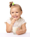 Little girl drinks milk using drinking straw Stock Photo