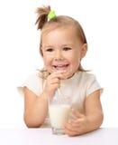 Little girl drinks milk using drinking straw. Cute little girl drinks milk using drinking straw, isolated over white Stock Photo