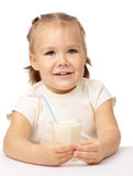 Little girl drinks milk using drinking straw Stock Photos
