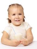 Little girl drinks milk using drinking straw. Cute little girl drinks milk using drinking straw, isolated over white Stock Photos
