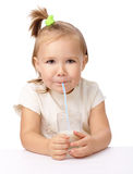 Little girl drinks milk using drinking straw Royalty Free Stock Image