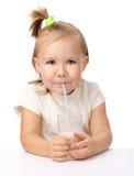 Little girl drinks milk using drinking straw. Cute little girl drinks milk using drinking straw, isolated over white Royalty Free Stock Image