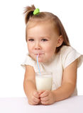 Little girl drinks milk using drinking straw. Cute little girl drinks milk using drinking straw, isolated over white Royalty Free Stock Images