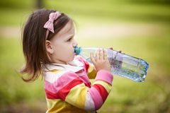 Little girl drinks mineral water Stock Photo