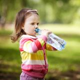 Little girl drinks mineral water Stock Images