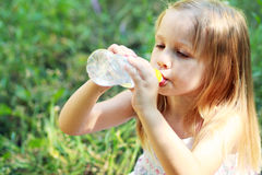 Little girl drinks mineral water Royalty Free Stock Images