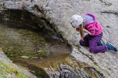 Girl drinks from a mountain stream in early spring Royalty Free Stock Images