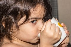 Little girl drinks from a mug of tea or juice. child nutrition issues. stock photography