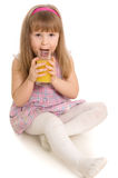 The little girl drinks orange juice Royalty Free Stock Images