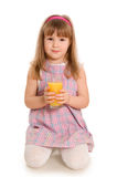 The little girl drinks orange juice Stock Photo