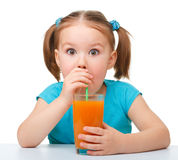 Little girl drinks orange juice Stock Photography