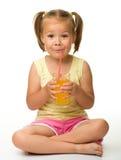Little girl drinks orange juice Royalty Free Stock Photos