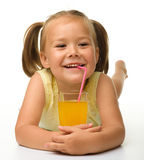 Little girl drinks orange juice stock images