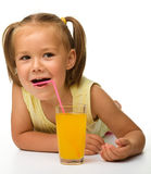 Little girl drinks orange juice Stock Photos