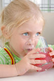 The little girl drinks a pink drink Stock Images