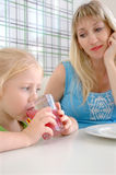 The little girl drinks a pink drink Royalty Free Stock Photos