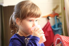 Little girl drinks. From a plastic cup Royalty Free Stock Photography