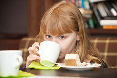 Little girl drinks tea with cake Royalty Free Stock Image