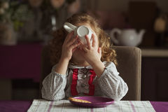 Little girl drinks tea from a large cup Royalty Free Stock Image