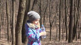 Little girl drinks water from a bottle. 4K UltraHD, UHD stock video footage