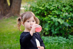 Little girl drinks water from a bottle on the nature park Stock Image