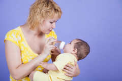 Little girl drinks water on the hands of moms Royalty Free Stock Photos