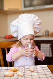 Little girl drinks water on kitchen using glass Royalty Free Stock Images