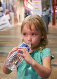 Little girl drinks water from a large bottle. Stock Photos
