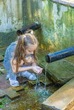 Little girl drinks water from source Stock Photo