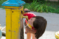 Little girl drinks water from a well. Teen girl drinks water from a chink  in the summer park Stock Images