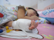 Little girl on a drip receiving a saline solution royalty free stock image