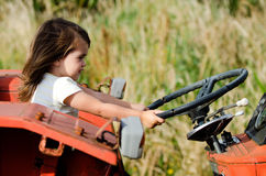 Small child sitting on an old tractor Stock Photo